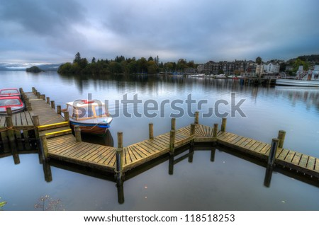Landscape image of a wooden jetty on Lake Windermere in Lake District, a National Park in England, during Autumn with grey sky and colourful boats next to jetty