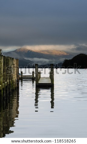 Landscape image of a wooden jetty on Lake Windermere in Lake District, a National Park in England, during Autumn with grey sky and view to the distant mountains.