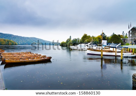 Landscape image of  Lake Windermere in Lake District, a National Park in England, during Autumn with grey sky, and colourful boats next to jetty