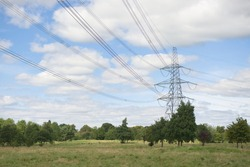 Landscape image of large metal electricity pylon and overhead power lines in a rural countryside setting. Summer season and green trees on the land