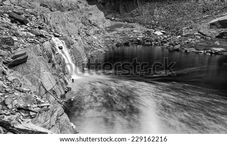 Landscape image of waterfall flowing into old abandoned quarry black and white