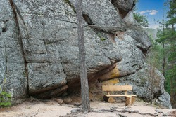 Landscape in forest with wooden bench for relaxing under giant rock in the Stolby Nature Reserve in Krasnoyarsk, Russia