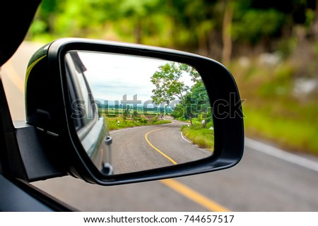 Landscape in the sideview mirror of a car , on road countryside. #744657517
