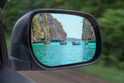 Landscape in the sideview mirror of a car , on road countryside. In the side mirror of the car is reflected the sea of rocks and boats. The concept of choosing to travel by car or sail on a boat.
