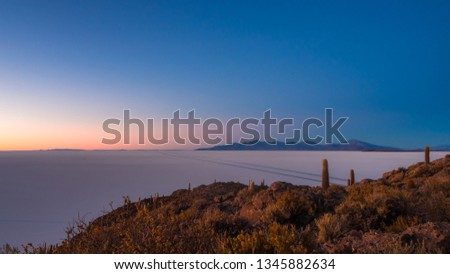 Landscape in Uyuni salt flat during the sunrise, with the road and mountains. pic from Inka Huasi island, Bolivia