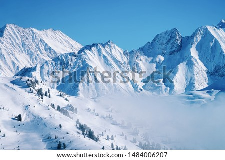 Landscape in Zillertal Arena ski resort in clouds in Tyrol at Mayrhofen in Austria in winter Alps. Alpine mountains with white snow and blue sky. Downhill peaks at Austrian snowy slopes.