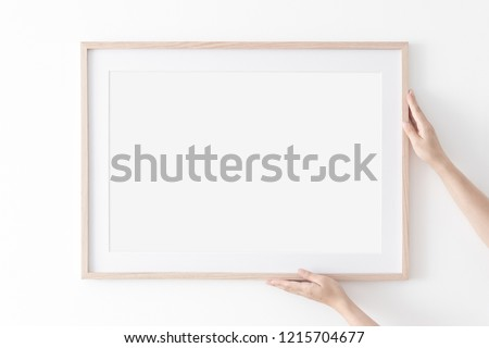 Landscape large 50x70, 20x28, a3,a4, Wooden frame mockup with passe-partout on white wall in women hands. Poster mockup. Clean, modern, minimal frame. Empty fra.me Indoor interior, show text or