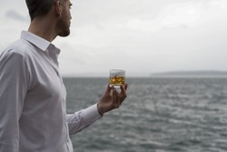 Landscape man holding whiskey on ice drink looking out to sea from the shore