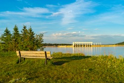 Landscape of a bench overlooking ghost lake and the Ghost Hydroelectric dam west of cochrane alberta, Canada