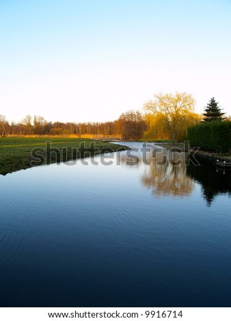 Landscape of a forest reflecting in the water with the setting sun lighting the trees