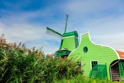 Landscape of a village with a windmill and a house. Famous Dutch Landscape - Agricultural Historical Landscape. Tourism. Popular Holland, Netherlands, Europe.