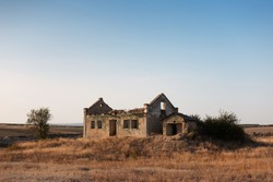 Landscape of abandoned house in dry field.