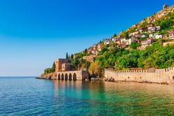Landscape of ancient shipyard near of Kizil Kule tower in Alanya peninsula, Antalya district, Turkey, Asia. Famous tourist destination with high mountains. Part of ancient old Castle. Summer day