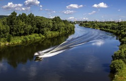 Landscape of banks of the river, speed boat on the river, summer day.View from above.