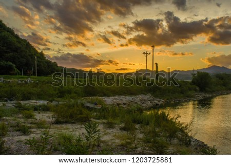 Landscape of beautiful sunset with puffy clouds in sky over inlet shore with a small fishing boat on shore next to waters edge.  #1203725881