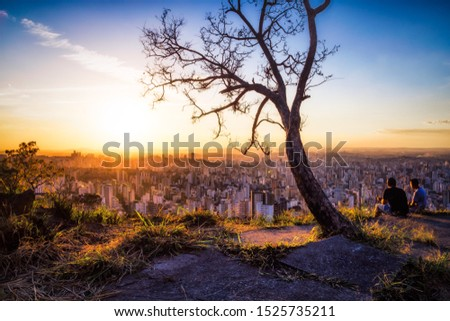 Landscape of Belo Horizonte City seen from Water Tank Gazebo (Mirante da Caixa D'Água) With a Loving and Romantic Couple Enjoying the View of a Colorful Sunset, Located in Minas Gerais State, Brazil