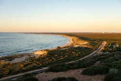 Landscape of coastline near Coastline and Vlamingh Head Precinct lighthouse at sunset with antenna array in the background