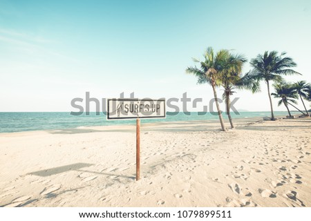 Landscape of coconut palm tree on tropical beach in summer. beach sign for surfing area. Vintage effect color filter.