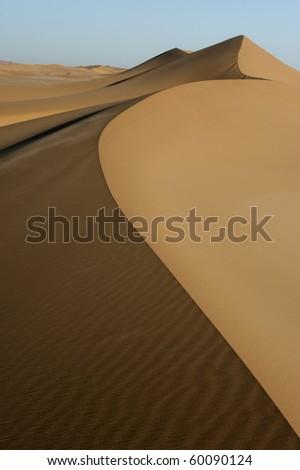 Landscape of desert sand dunes that streches into the horizon.
