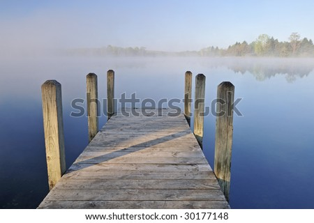Landscape of dock and foggy, spring shoreline Whitford Lake, Fort Custer State Park, Michigan, USA