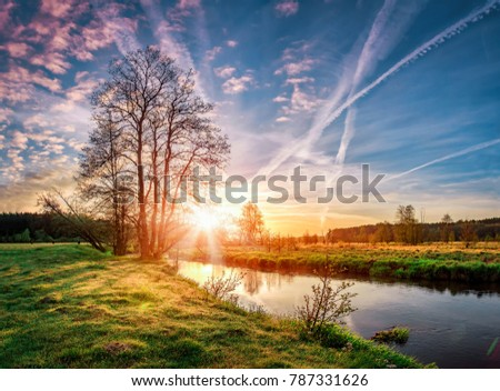 Landscape of early spring at morning sunrise on river. Bright sun lights through trees on horizon. Beautiful spring nature.