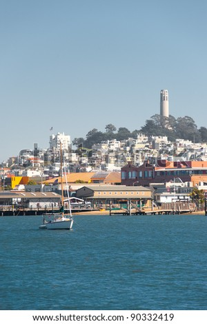 Landscape of famous Coit Tower on Telegraph Hill is seen behind a calm waterfront bay with a lone sailboat on a clear sunny, blue sky day in San Francisco, California. Vertical copy space