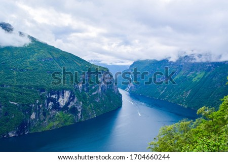 Landscape of Geirangerfjord and Seven Sisters Waterfall near small village of Geiranger. View from Eagles Road viewpoint. Summer travel adventure to Norway.
