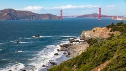 Landscape of Golden Gate bridge over sea horizon from Baker beach, San Francisco, California, USA.
