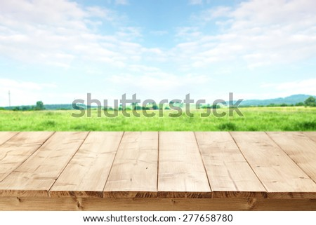 landscape of grass and sky of blue color with free space on table of wood