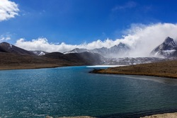 Landscape of Gurudongmar Lake with rocks in forte ground and mountain with blue sky in background. Gurudongmar lake one of the highest lake of the world and India located at an altitude of 17,800 ft.