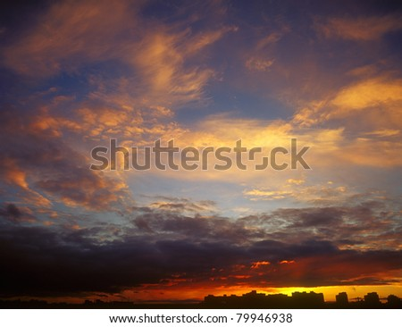 Landscape of houses silhouetted against a sunset.