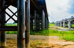 Landscape of iron substructure of bridge under construction over river next to existing concrete bridge.