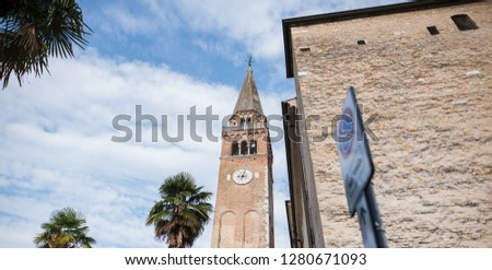 Landscape of Italian arhitecture over background of blue sky and palm tree.
