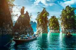 Landscape of Khao Sok National Park with longtail boat for travelers, Cheow Lan lake, Ratchaphapha dam, Travel nature in Thailand, Beautiful destination place Asia, Summer outdoor vacation travel trip