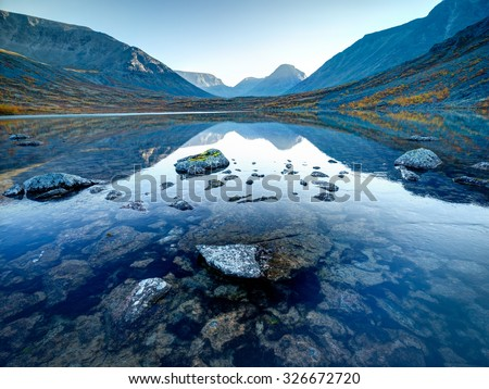 Landscape of lake Tahtarjavr with transparent water, rocky bottom and distant mountains reflected in still morning waters, Hibiny mountains above the Arctic circle, Russia #326672720