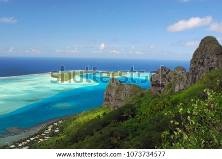 Landscape of Maupiti island showing the mountain top, the lagoon and a small village on a sunny day in French Polynesia #1073734577