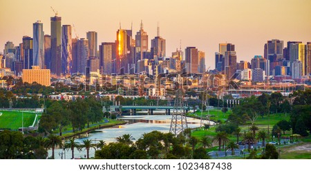 Landscape of Melbourne City over Maribyrnong River and Footscray Park. Crowded modern office buildings in Melbourne's CBD in sunset.  #1023487438