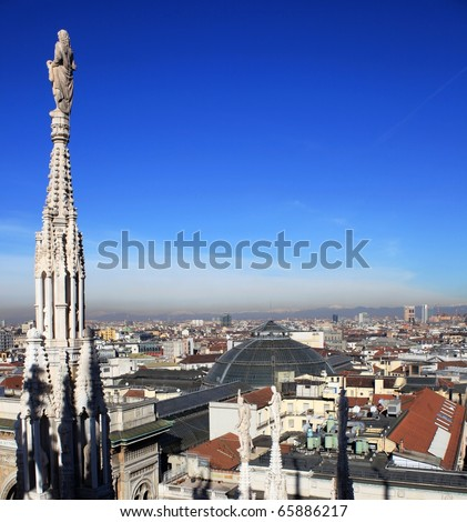 Landscape of Milan from the roof of Duomo cathedral, blue sky on the background.