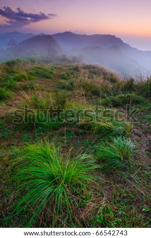 Landscape of misty mountain at sunrise with grass foreground - stock photo
