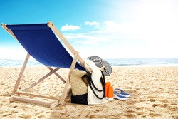 landscape of ocean and beach with chair bag and hat
