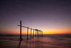 landscape of old wooden bridge with colorful sky in twilight time at Natai, Khok Kloi, Takua Thung District, Phang-nga, Thailand.