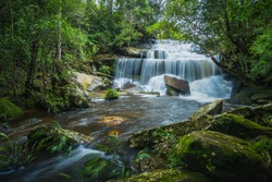 Landscape of peaceful waterfall with green moss in the tropical rainforest