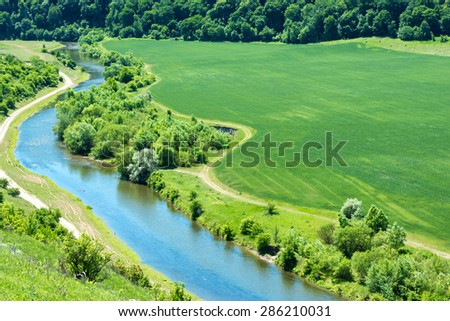 Landscape of river, green wheat field with nearby forest and country road passing by