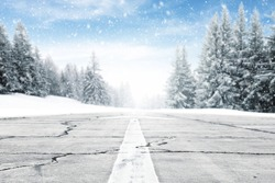 landscape of sky and trees of snow and gray road