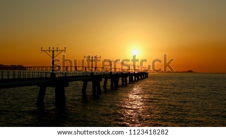 Landscape of sunset and silhouette of a long pier bridge. #1123418282