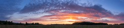 Landscape of sunset panorama of summer field with green grass in evening twilight under blue sky with clouds in bright sunset light colorful panoramic view of field in sunset dusk with trees silhouett