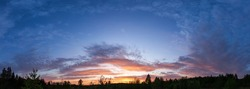 Landscape of sunset panorama of summer meadow with trees silhouette in evening twilight under blue sky with clouds in bright sunset light, colorful panoramic view of field in sunset dusk.