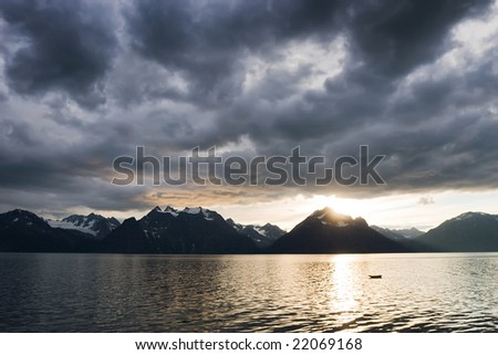 landscape of sunset with dark clouds above a lake with snow mountains coast