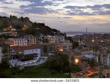 Landscape of the city of Lisbon at dusk, with lit street lamps and cloudy sky.