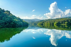Landscape of the dam and lake on the mountain with tree and forest, The river and beautiful blue sky and clouds on sunshine day.